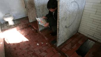 Un hombre lee en un baño público en Beijing, China