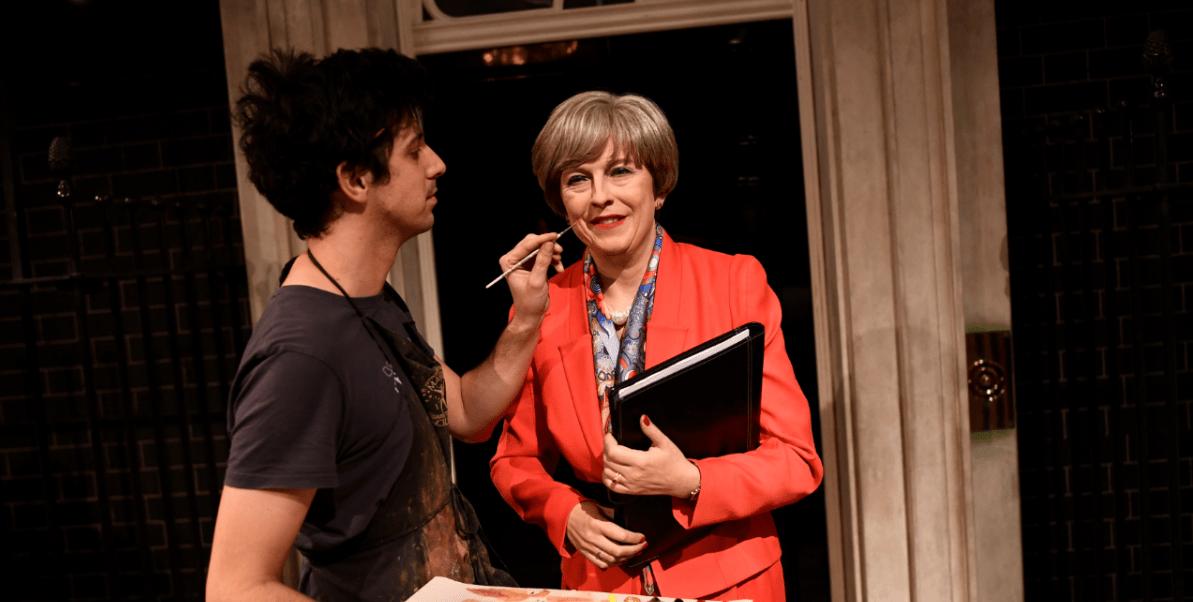 Un hombre retoca la figura de cera de Theresa May