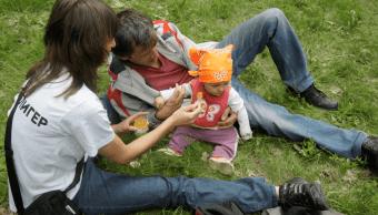 Una pareja rusa alimenta a su bebé en un parque de Moscú
