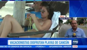 Turistas disfrutan las playas de Cancún