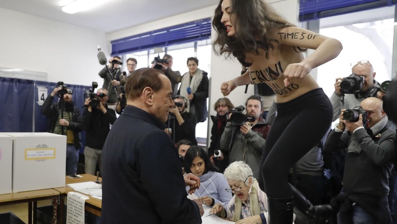 Una activista sin camiseta interrumpe a Berlusconi cuando votaba