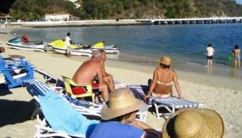 Turistas disfrutan las playas de Huatulco, en Oaxaca