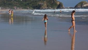 Miles de turistas disfrutan de la playa en Zipolite, Oaxaca