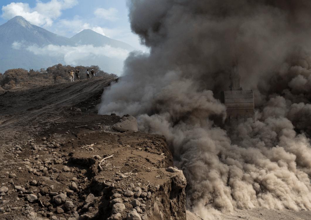 Una pala mecánica provoca nubes de cenizas durante la reparación de una carretera en Guatemala. (AP)