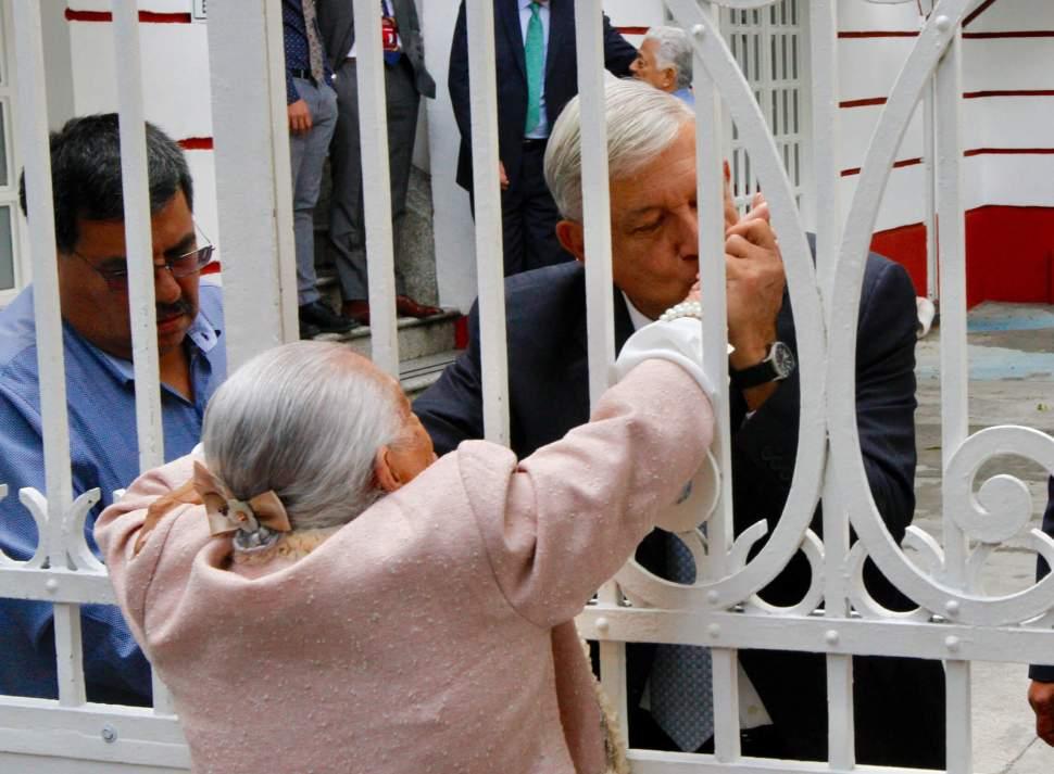 AMLO besa la mano de una mujer afuera de casa de transición