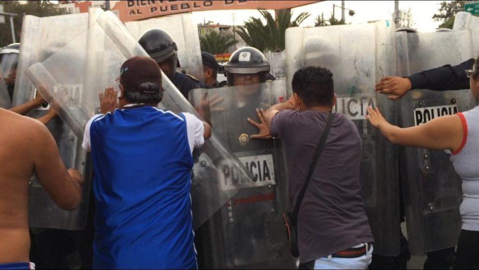 Granaderos enfrentan a padres de familia en protesta