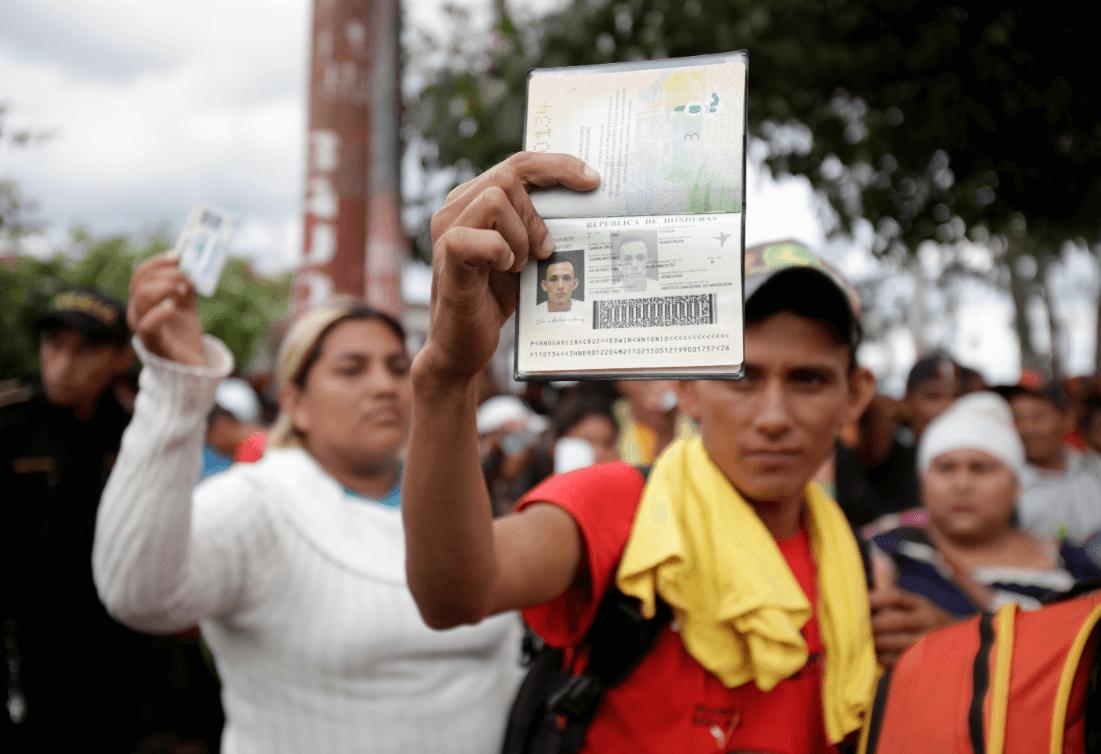 Migrantes hondureños muestran su identificación en Guatemala. (AP)