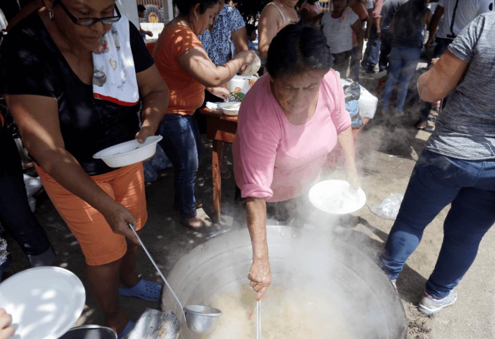 Voluntarios ofrecen comida a migrantes en Guatemala. (AP)