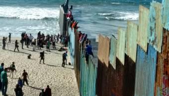 Caravana migrante se trepan a valla fronteriza en Tijuana