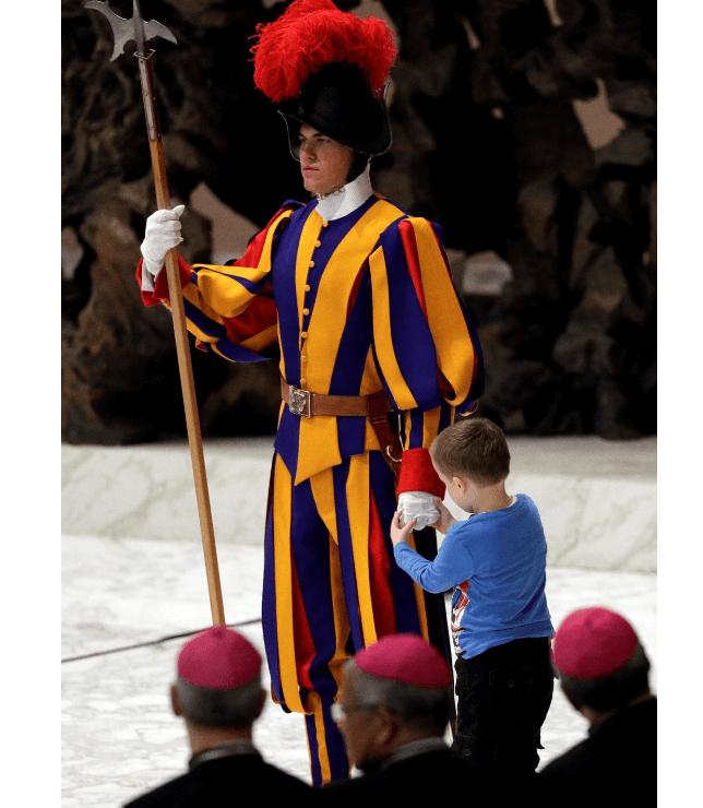 Niño juega con miembro de la Guardia Suiza. (AP)