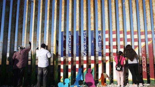 Foto: Una familia migrante protesta en la valla fronteriza entre San Diego y Tijuana