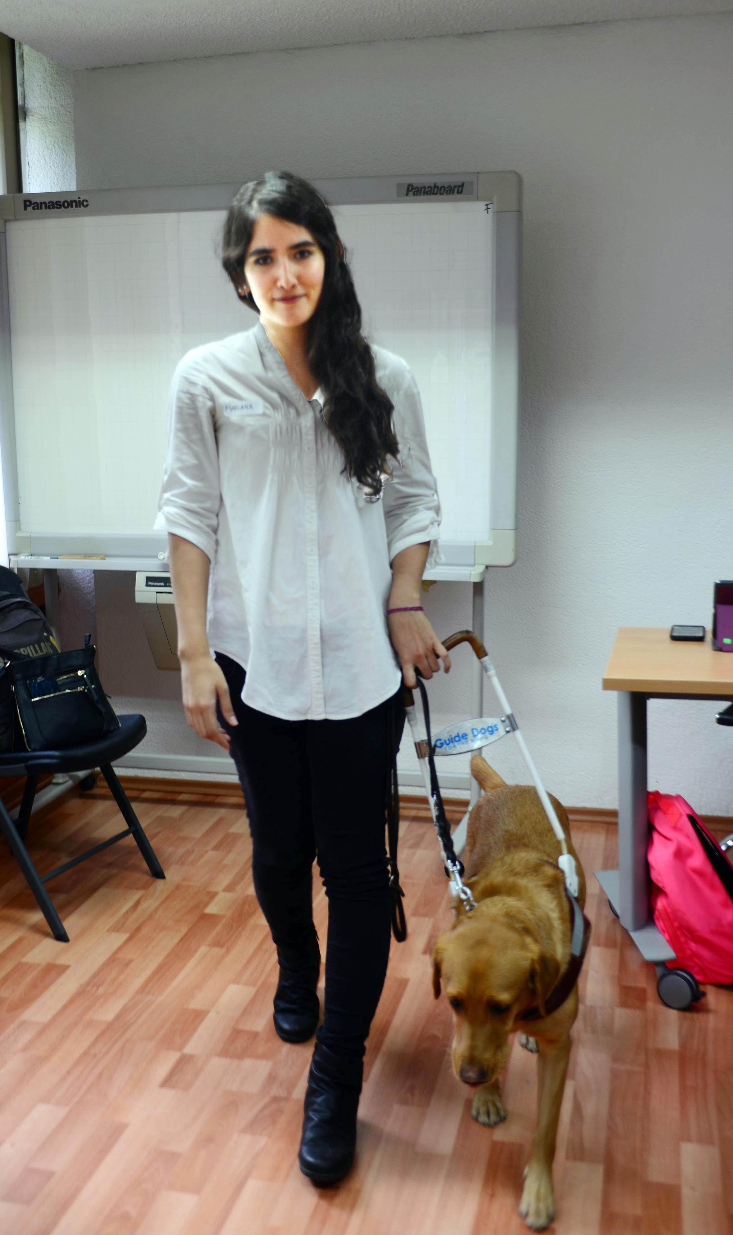 Karla Mariana Escobar Magallanes sonríe junto a su perrita guía, Yzma, tras realizar su exámen profesional (DGCS UNAM)