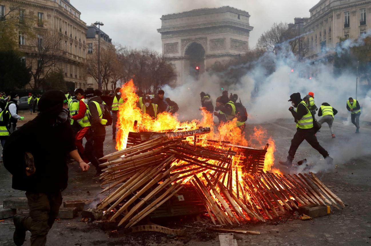 Los manifestantes provocaron incendios y fogatas cerca del Arco del Triunfo, al centro de la Plaza Charles de Gaulle (AP Images)