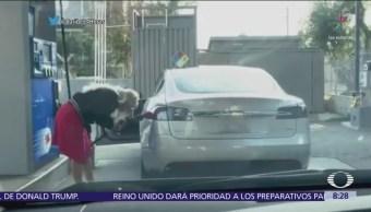 Mujer intenta poner combustible a un carro eléctrico