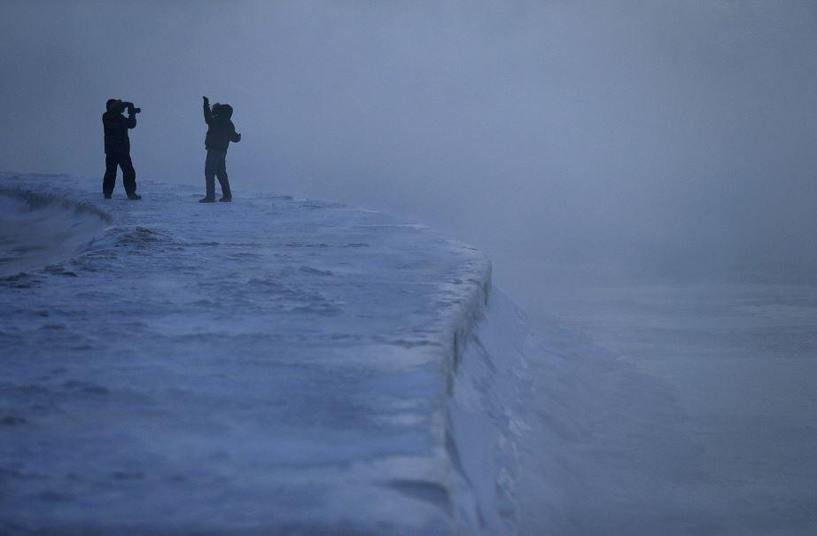 Foto: Un hombre posa para una foto mientras el hielo se forma a lo largo de la orilla del lago Michigan