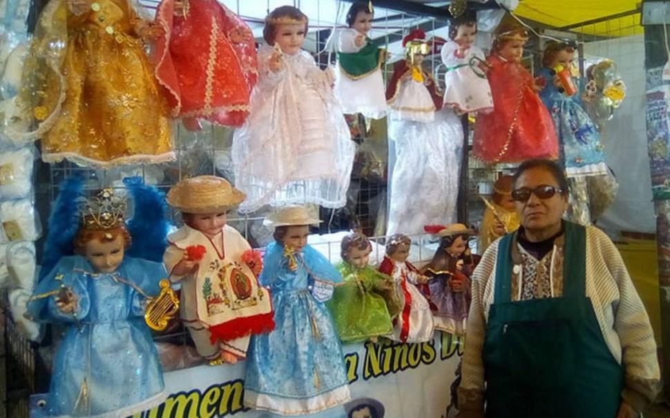 Una vendedora junto a su puesto de niños Jesús vestidos para el Día de la Candelaria (Puebla Hoy)