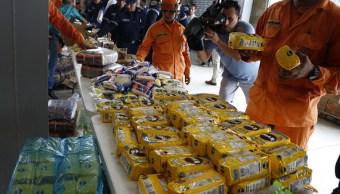 Foto: Miembros de la brigada de bomberos en Colombia acomodan en paquetes de ayuda humanitaria que se serán enviados a Vezuela, 14 febrero 2019