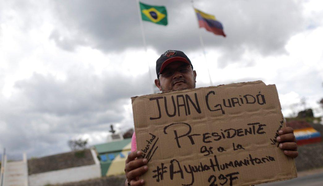 """Foto: Un venezolano muestra un cartón que dice: """"Presidente de Juan Guaido; sí a la ayuda humanitaria"""" en la ciudad fronteriza de Pacaraima, en Roraima, Brasil, 21 de febrero de 2019"""