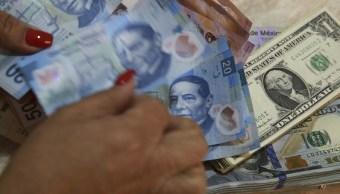 Foto: Un empleado de banco cuenta los billetes en pesos mexicanos además de los billetes en dólares estadounidenses en la Ciudad de México, México, febrero 5 de 2019 (Getty Images)