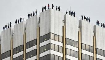 Foto: Escultura de hombres en el techo de un edificio en Londres que intentan suicidarse, febrero 6 de 2019 (Getty Images)