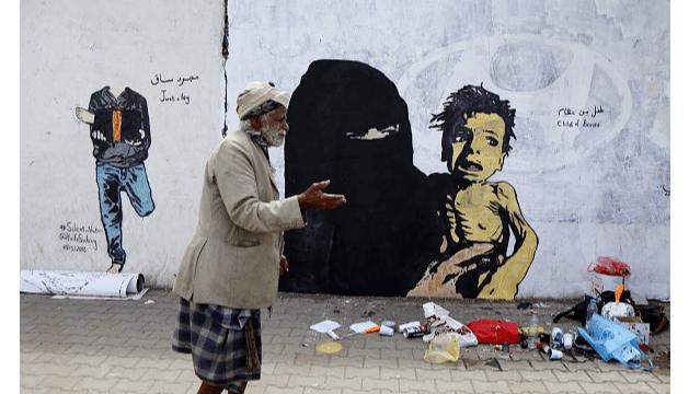 Un hombre en Yemen camina frente a un grafiti, 21 de febrero de 2019, Sana, Yemen