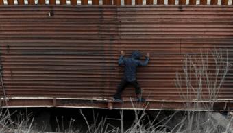 Foto: Un migrante centroamericano intenta cruzar la valla fronteriza en Tijuana, 6 diciembre 2018, México
