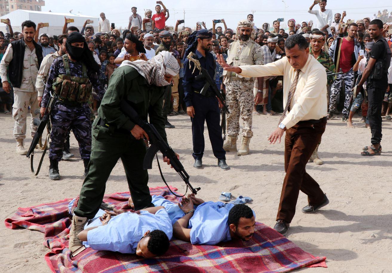 Un militar apunta un arma larga contra las espaldas de Refat y Khaled, sentenciados a muerte por secuestro, violación y asesinato de un menor de edad (Reuters)