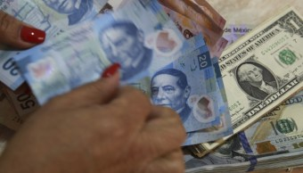 Foto: Un trabajador cuenta los billetes en pesos mexicanos además de los billetes en dólares estadounidenses en una tienda de cambio en Ciudad de México, marzo 11 de 2019 (Getty Images)