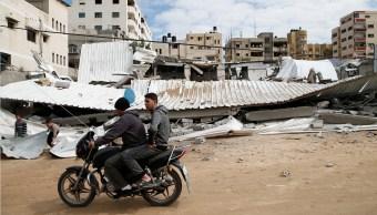 Fotos: Dos palestinos pasan en una motocicleta cerca de un sitio de Hamas destruido por bombardeos israelíes en la ciudad de Gaza. El 12 de marzo de 2019