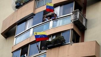 Foto: Dos hombres ondean banderas de Venezuela desde las ventanas de un edificio en Caracas, el 12 de marzo del 2019