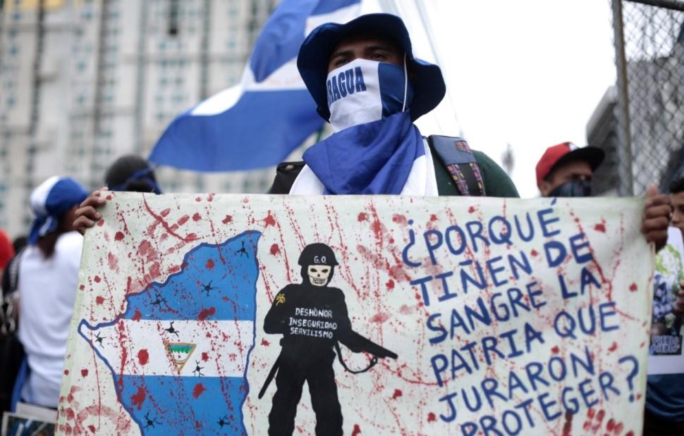"""Foto: Un nicaragüense muestra una pancarta que dice """"Porque mancharon de sangre el país, juraron proteger"""", durante una protesta, febrero 27 de 2019 (Reuters)"""