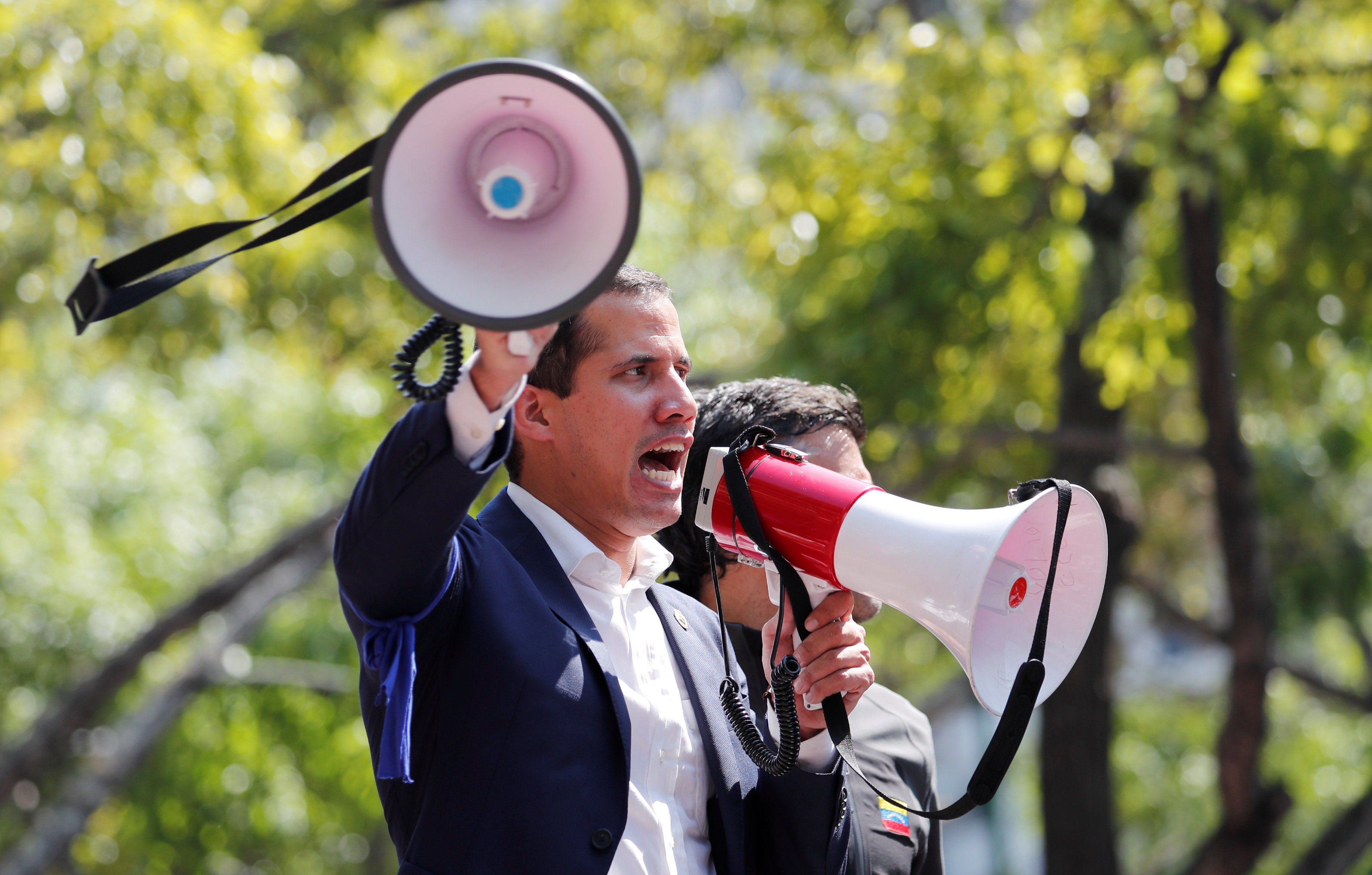 El líder de oposición Juan Guaidó ha sido reconocido como el presidente interino legítimo de Venezuela por diversas naciones. En esta foto, Guaidó cambia de megáfono para proclamarse ante una multitud (Reuters)