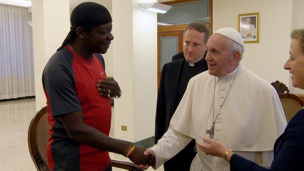 El momento en el que el actor británico Stephen K. Amos da un saludo de mano al Papa Franciso tras una charla sobre la homosexualidad (BBC)