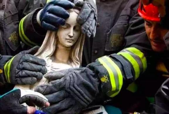 Foto: Un grupo de bomberos tocan la estatua de mármol de Madonna después de retirarla de la iglesia de Paganica, cerca de Aquila, Italia. El 13 de abril de 2009