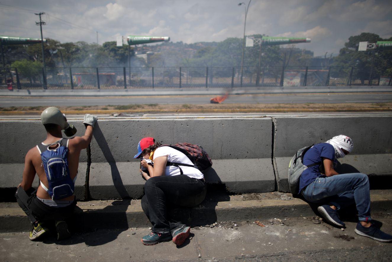 Gente que apoya el levantamiento militar se resguarda en una de las barreras de concreto de la autopista frente a la base militar 'La Carlota' (Reuters)