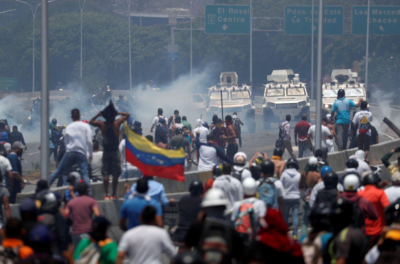 Manifestantes de oposición se enfrentan a tanquetas militares, utilizadas para disuadir las protestas por el régimen de Nicolás Maduro (Reuters)