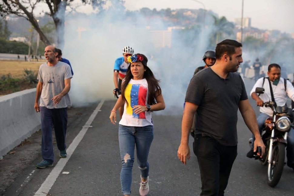 Pobladores de Caracas que salieron a las calles ante el llamado de Guaidó huye de los gases lacrimógenos (Reuters)