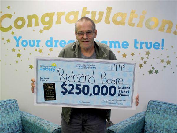 Richard Beare, ganador de la lotería 'scratch-off' en Carolina del Norte, posa frente a la cámara sosteniendo su cheque de 250 mil USD (NCLottery)