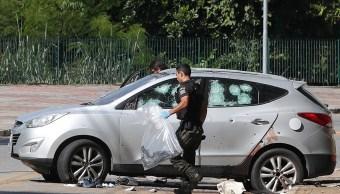 Foto: Un oficial de policía recoge una pistola en el lugar donde se enfrentaron a un grupo armado que intentó robar un banco en Guararema, Brasil, 4 abril 2019