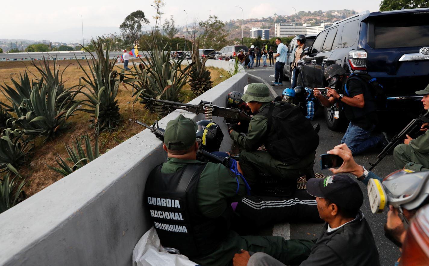 Soldados que apoyan el levantamiento militar de Juan Guaido toman cubierta ante el sonido de múltiples disparos provenientes de la base 'La Carlota' (Reuters)