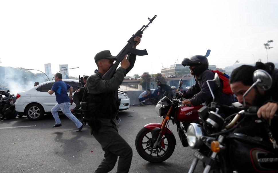 Soldados y gente reaccionan ante el sonido de disparos cerca de 'La Carlota'. Algunos toman cubierta y otros huyen en vehículos (Reuters)