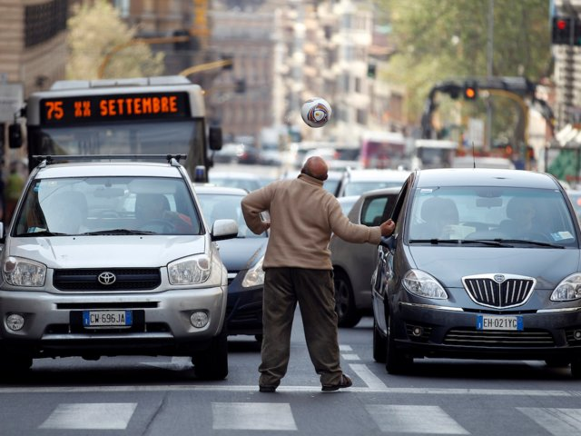 Un hombre pide dinero después de concluir una rutina de entrenamiento de futbol en las calles de Roma (Reuters)