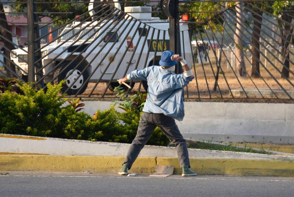 Un manifestante de la oposición arroja piedras a vehículos militares dentro de la base 'La Carlota' (El País)
