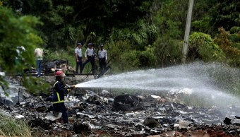 Foto: Un bombero lanza agua a los restos de un avión Boeing 737 que se estrelló en el área agrícola de Boyeros, en La Habana, Cuba. El 18 de mayo de 2018