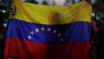 Foto: Una mujer sostiene una bandera de Venezuela mientras participa en una vigilia en Caracas. El 5 de mayo de 2019