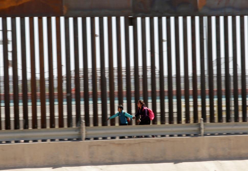 Foto: Dos migrantes corren para solicitar asilo después de cruzar ilegalmente la frontera en El Paso, Texas, EEUU. El 21 de abril de 2019