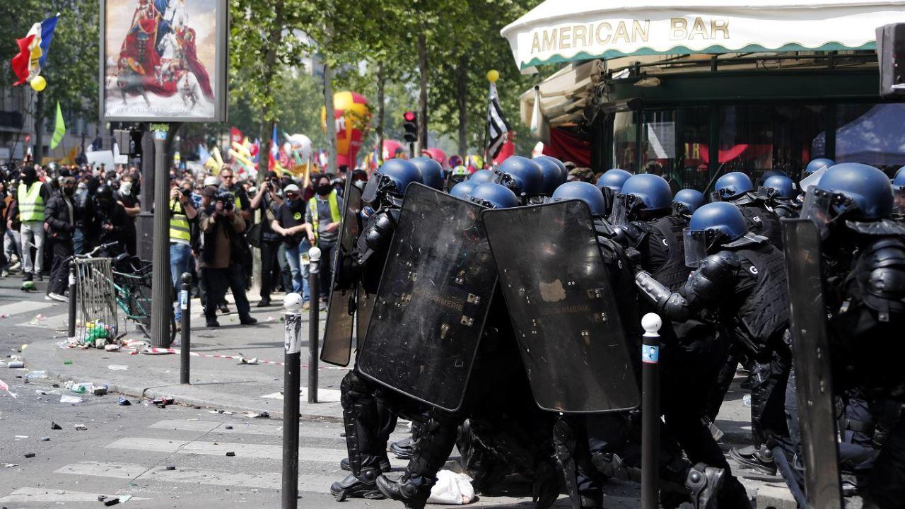 fOTO: La policía antidisturbios se protege del lanzamiento de proyectiles por parte de los manifestantes, 1 mayo 2019