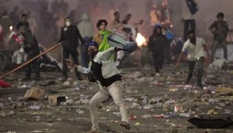 Foto: Partidarios del candidato presidencial indonesio, Prabowo Subianto, lanzan piedras a la policía antidisturbios durante los enfrentamientos en Yakarta, 23 mayo 2019