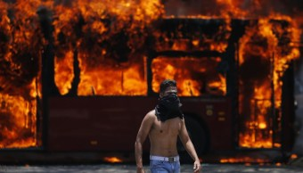 Foto: Un manifestante antigubernamental camina cerca de un autobús incendiado por opositores a Nicolás Maduro, 1 mayo 2019