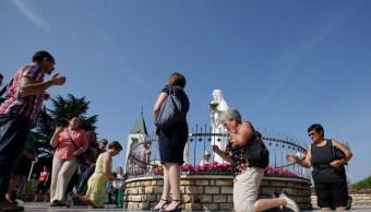 Foto: Los peregrinos rodean la estatua de la Virgen María frente a la Iglesia de Santiago en Medjugorje, 12 mayo 2019